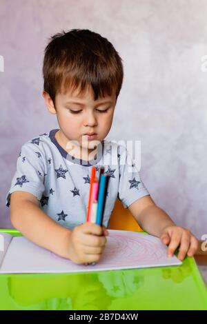 Petit garçon dessin avec des crayons de couleurs. Petit garçon est la tenue des crayons de couleurs. Il y a beaucoup de crayons de couleur dans les mains du garçon. Petit garçon dessine à la Banque D'Images