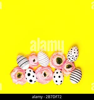 Graphique créatif et œufs peints à la main, Ranunculus fleurs sur fond jaune vif. Concept de Pâques.