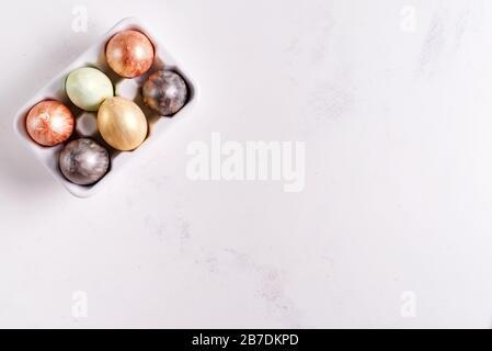 Plateau d'œufs en céramique avec œufs de Pâques peints en or et en argent sur fond de pierre blanche, concept de vacances