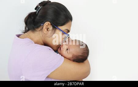 une jeune mère en lunettes embrassant son bébé garçon dans son tour dans un fond gris solide avec de l'espace pour le texte. mère jour photo concept. Banque D'Images