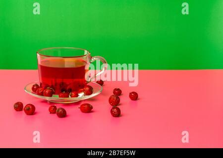 Une tasse avec une infusion de baies de rosehip séchées sur une table avec réflexion. Fond vert. Banque D'Images