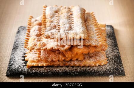 Chiacchiere italienne spécialisée, biscuits carnaval doux de pâte croustillante frite saupoudrée de sucre en poudre empilée sur un plateau en gros plan Banque D'Images