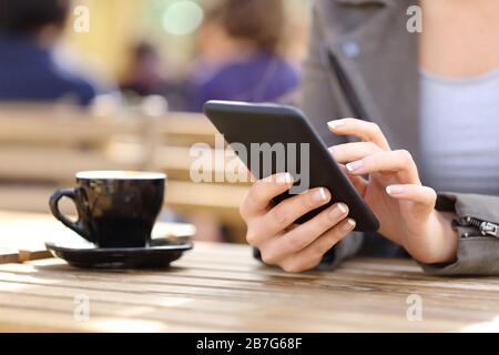 Gros plan sur les mains de la femme à l'aide de son téléphone portable sur une terrasse de café
