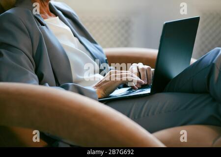 Portrait court d'une femme d'affaires moderne et mûre travaillant avec un ordinateur portable tout en étant assis dans une chaise en cuir au bureau, espace de copie Banque D'Images