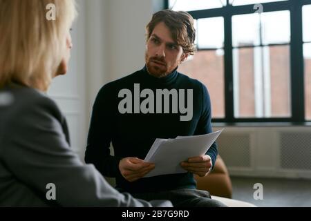 Taille vers le haut portrait de l'homme barbu barbu à la femme partenaire tout en discutant de travail à l'intérieur de bureau, espace de copie Banque D'Images