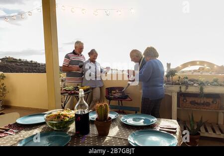 Les couples seniors heureux mangeant et buvant du vin au barbecue dîner en plein air - les personnes âgées ayant des repas amusants et riant ensemble - foyer principal sur la gauche Banque D'Images