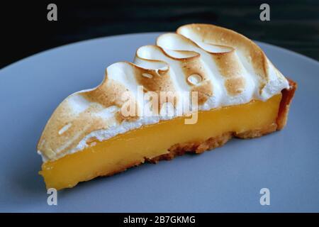 Gros plan savoureux citron Meringue Tart sur Blue Gray plate Banque D'Images