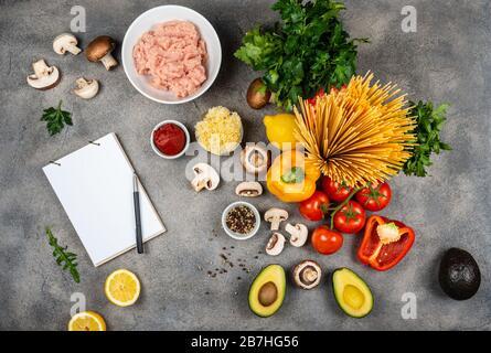Différents légumes et ingrédients pour faire des pâtes. Un livre pour écrire des recettes se trouve sur la table. Espace de copie pour le texte Banque D'Images