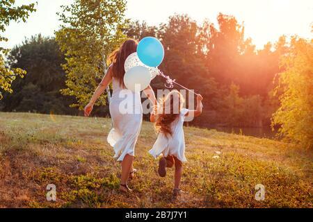 Fête des mères. Petite fille courir avec la mère et tenir des balons dans la main. Famille s'amuser dans le parc d'été Banque D'Images