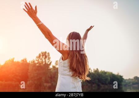 Femme d'âge moyen mûre profitant du coucher du soleil avec des bras élevés se sentant heureux dans le parc de printemps. Femme senior admire le paysage