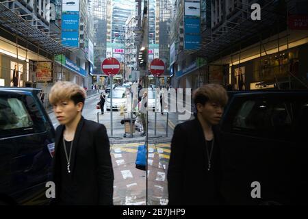 Homme d'âge moyen sur la rue de Hong Kong se reflète dans la fenêtre miroir, scène de rue Banque D'Images