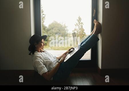 Une fille hipster élégante assise au sol avec un ordinateur portable dans une grande fenêtre avec vue sur la forêt. Jeune femme heureuse en chapeau en utilisant un ordinateur portable, des magasins ou en travaillant onli