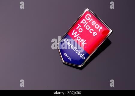 Broche broche avec le texte Grand lieu de travail sur une surface de relief rouge et bleu réfléchissant sur un fond gris dégradé. TRADUCTION: 'CERTIFIÉE. BRAZI