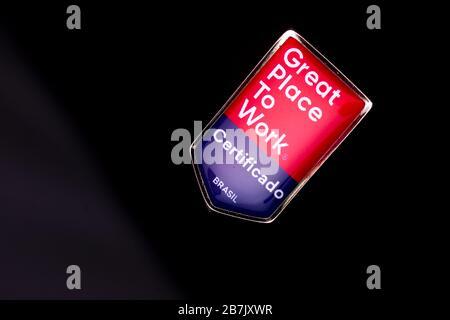 Badge avec le texte Grand lieu de travail sur une surface de relief réfléchissante rouge et bleu sur un fond noir. TRADUCTION: 'CERTIFIÉE. BRÉSIL »