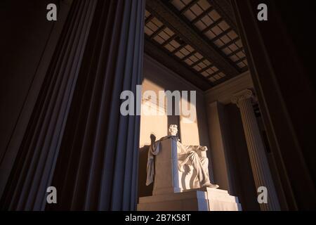 WASHINGTON DC, USA - La grande statue à l'intérieur de la chambre principale du mémorial Lincoln attraper tôt le matin au lever du soleil d'or au cours de l'automne (automne) equinox. Le Lincoln Memorial est situé sur l'extrémité ouest de la Reflecting Pool et fait face directement à l'Est. La statue est profond au sein de la chambre et est normalement bien hors de portée de la lumière du soleil directement.