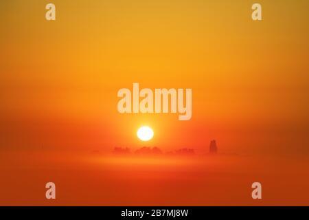 Paysage rural. Un lever de soleil orange magique sur le terrain, un matin brumeux. Paysage minimaliste Banque D'Images