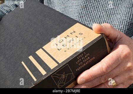 Homme transportant tenant la livraison en ligne d'Internet de John Lewis boîte colis Angleterre Royaume-Uni GB Grande-Bretagne Banque D'Images