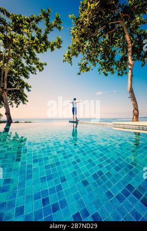 Une jeune femme pratiquant le yoga sous des palmiers à côté d'une piscine à débordement