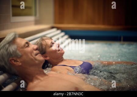 Un couple d'âge mûr heureux se détendant ensemble dans un spa. Banque D'Images