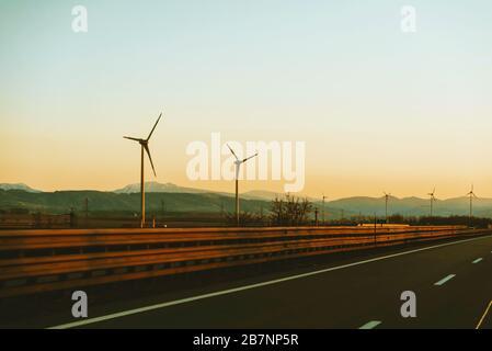 Photo de l'énergie éolienne, allez au vert, éoliennes le long de la route au coucher du soleil Banque D'Images
