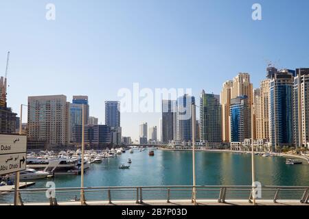 Gratte-ciel et bateaux de la marina de Dubaï dans le port en une journée ensoleillée, ciel bleu clair à Dubaï, Emirats Arabes Unis Banque D'Images