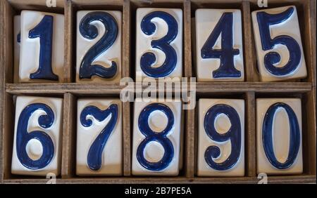 Carreaux de céramique bleu et blanc avec numéros élevés 0 à 9 disposés en deux rangées dans une boîte en bois. Banque D'Images