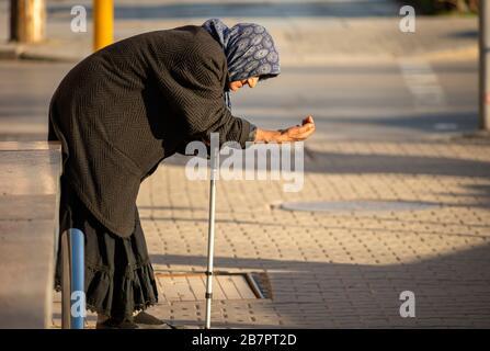 Une vieille femme mendière femme senior portant des vêtements noirs et tenant un bâton est mendiant pour l'argent dans les rues de Sofia Bulgarie