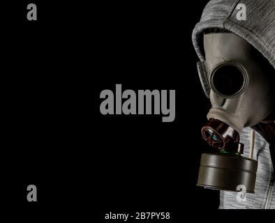 homme dans un masque à gaz sur fond noir. protection contre les virus