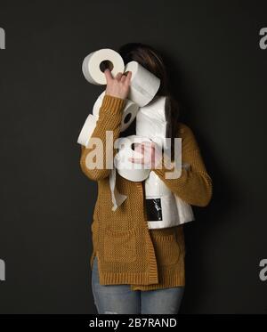 Une femme tient une pile de fournitures de papier toilette pour un concept de demande des consommateurs concernant la pandémie du virus corona.