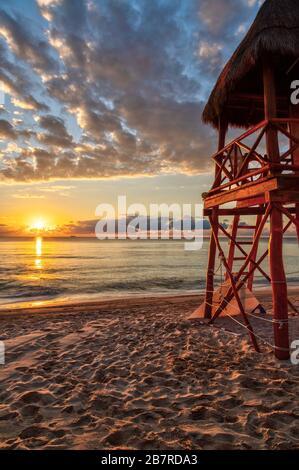 Lever du soleil sur les plages tropicales de la Riviera Maya près de Cancun, au Mexique, avec tour de sauveteur surplombant la mer des Caraïbes. Orientation verticale.