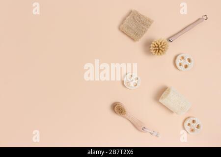Disposition des brosses en bambou et loofah sur un fond beige. Concept zéro déchet avec place pour le texte. Banque D'Images