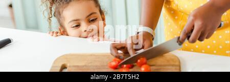 photo panoramique d'une femme africaine américaine qui coupe des tomates cerises à bord près d'une fille heureuse Banque D'Images