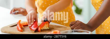 photo panoramique d'un enfant africain américain qui coupage le poivron près de la mère Banque D'Images