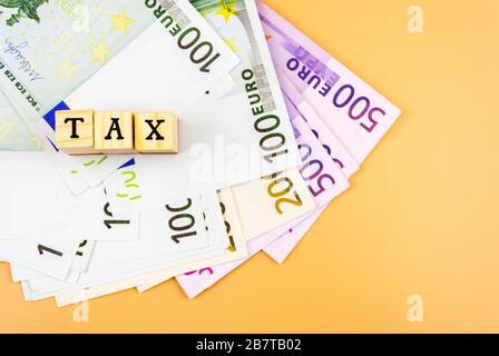 Le mot taxe et la monnaie de l'Union européenne de différentes dénominations sur un fond orange 4