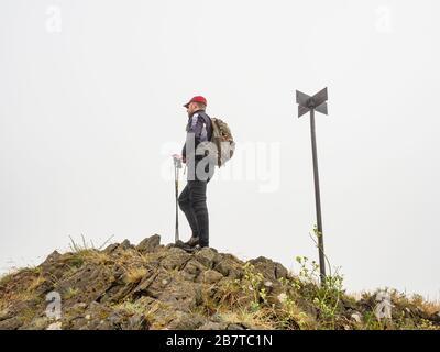 Seul routard transportant le sac à dos et en utilisant des bâtons de randonnée et en profitant de la vue sur la vallée