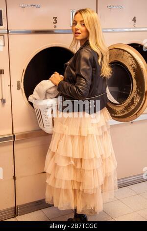 Jeune femme dans un sèche-linge à chargement par laverie Banque D'Images