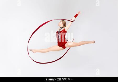 Charmant gymnast avec chaîne faisant saut en deux dans l'air sur fond blanc Banque D'Images