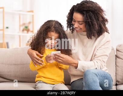 Mère africaine enseigner fille à utiliser smartphone assis sur canapé