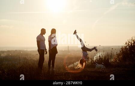 La mère et le père se tiennent sur la colline et regardent leur fille faire une main, derrière eux un bel horizon de vue d'un soleil couchant Banque D'Images