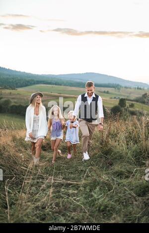 Famille heureuse en vêtements décontractés, mère, père et deux petites filles sur la nature, marche togethr tenant les mains, su mer coucher de soleil dans le champ sauvage dans
