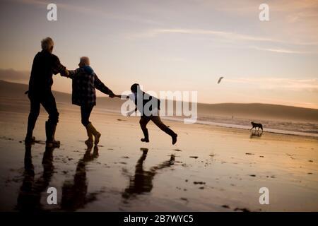 Un couple adulte mûr est tiré par son petit-fils adolescent le long d'une plage au coucher du soleil.
