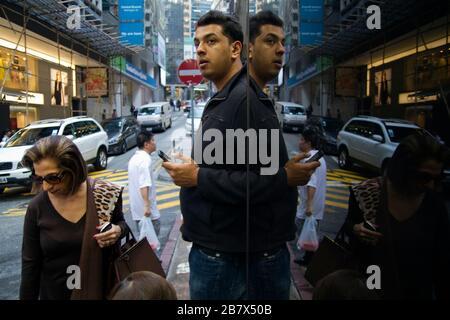 Homme et femme dans la rue de Hong Kong se reflètent dans la fenêtre miroir, scène de rue Banque D'Images