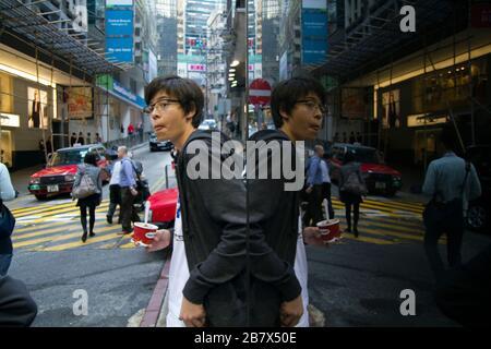 Jeune personne dans la rue de Hong Kong se reflète dans la fenêtre miroir, scène de rue Banque D'Images