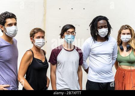 groupe de jeunes de différentes ethnies avec un masque sur leur visage à côté d'un mur Banque D'Images