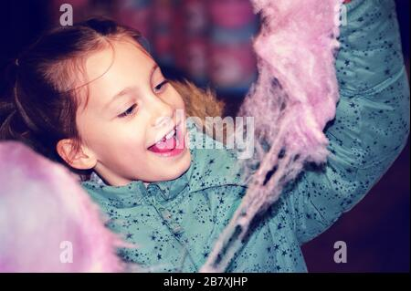 Jeune fille tenant coton Candy (Candy Foss). Une belle fille de 8 ans ne peut pas attendre de manger des bonbons floss au parc d'attractions. Banque D'Images