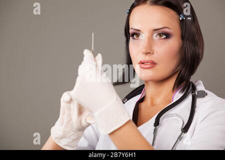 Gros plan portrait d'une belle femme à oeil brun médecin en gants médicaux tenant une seringue dans ses mains posant sur un fond gris. Concept de médicament Banque D'Images