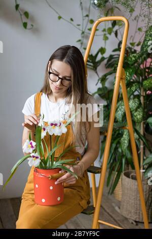 Jeune femme souriante jardinier dans des verres portant des combinaisons, en prenant soin de l'orchidée dans le vieux lait rouge peut se tenir debout sur l'échelle orange vintage. Jardinage à la maison