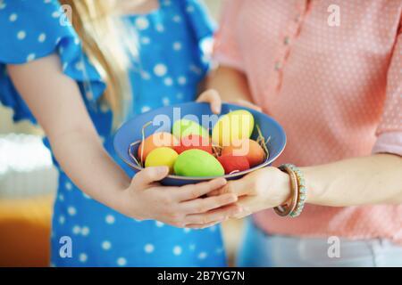 Gros plan sur la mère et la fille montrant une plaque bleue avec des œufs de pâques colorés à la maison dans le soleil de printemps.