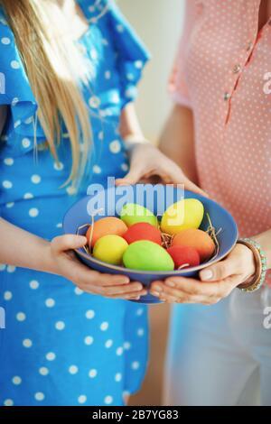 Gros plan sur la mère et l'enfant montrant une plaque bleue avec des œufs de pâques colorés dans le salon en journée ensoleillée de printemps.