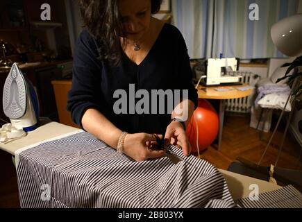 Prague, République tchèque. 18 mars 2020. Zuzana Kopeckova fabrique des masques avec un tissu à la maison à Prague, en République tchèque, le 18 mars 2020. En raison de la propagation rapide de COVID-19, la République tchèque est aujourd'hui confrontée à une pénurie d'équipements médicaux comme les masques. Zuzana travaille à une chaîne de télévision locale, mais elle travaille maintenant à la maison en raison de l'épidémie. Elle fait volontairement des masques pour les collègues et les amis à son temps libre. Crédit: Dana Kesnerova/Xinhua/Alay Live News